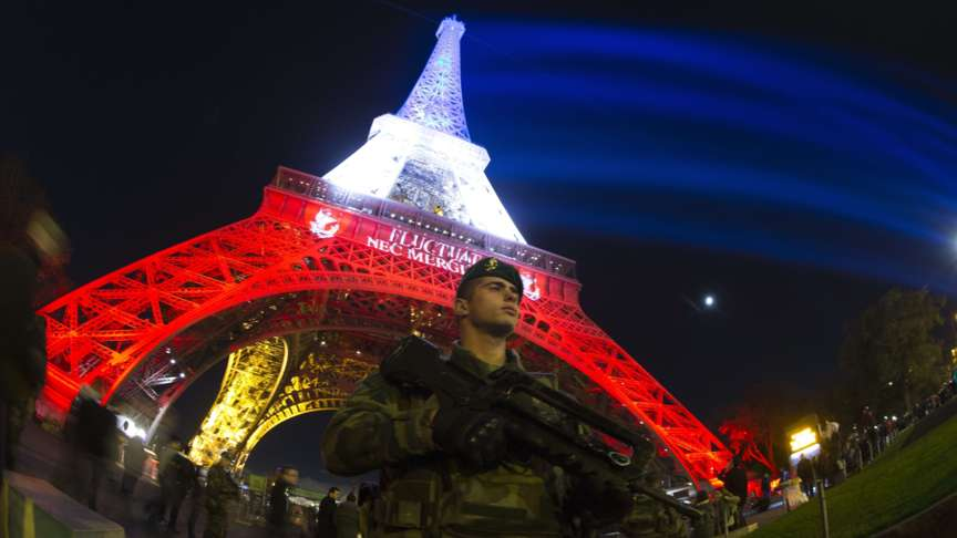 2015-11-18 21:23:06 A French soldier enforcing the Vigipirate plan, France's national security alert system, is pictured on November 18, 2015 in Paris in front of the Eiffel Tower, which is illuminated with the colors of the French national flag in tribute to the victims of the November 13 Paris terror attacks in which some 129 people were killed. AFP PHOTO / JOEL SAGET